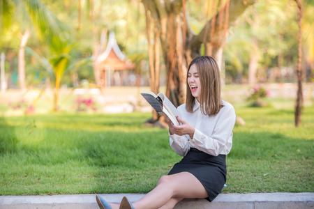 ミニを着て都市公園における本雑誌を読んで彼女がスカート笑って幸せなビジネスの女性と笑顔