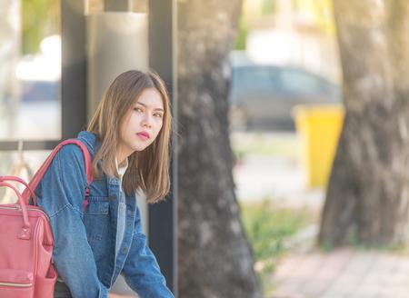 バスを待つより女の子。金属のベンチに座ってだけで考えると不満の感情を表現することを望んでの屋外の両親を十代待って退屈してください。 写真素材