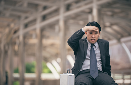 tired businessman: Businessmen sad worry tired sit with black bag on street Stock Photo