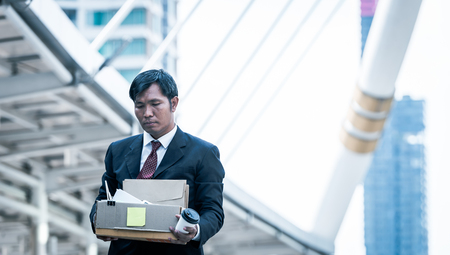 businessman holding holding cardboard box with personal belongings Leaving Job. Fired