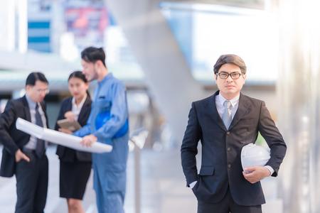ビジネス人々 のグループやチーム経営建設エンジニア リング アーキテクチャ管理事業計画のための青写真を押し安全帽子の作業をコンサルティン