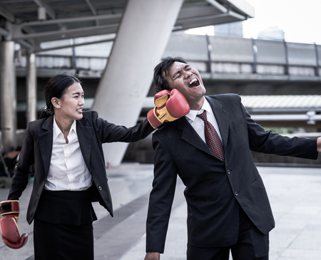 Business concept : Young Asian business woman in suit uniform wearing boxing gloves and punching business mans face Imagens