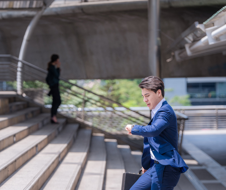 businessman in a hurry checking time and running, he is late for work his business appointment Stock Photo