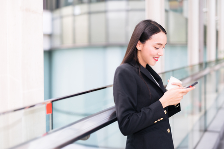 lady on phone: Young Asian woman with smartphone standing against street blurred building background. Fashion business photo of beautiful girl in black casual suite with phone and cup of coffee and use smartphone