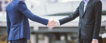 Business handshake concept. shaking hand of two businessman closing a deal city background