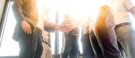 Business people join hand together during their meeting with sun rays aura background.