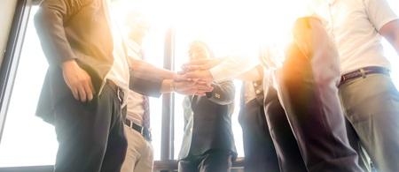 Mensen uit het bedrijfsleven hand in hand samen tijdens hun ontmoeting met zonnestralen aura achtergrond.