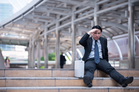 Stressed businessman sitting at stairway outdoor.Bankrupt businessman sitting outdoor. Stockfoto