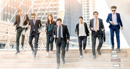 Portrait of hurrying people in suits run forwards for work with optimistic expression.Business people running in city .Team work rush hour and competition concept Stock Photo
