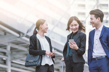 Groep Aziatische bedrijfscollega's die mobiele telefoon buiten het bureau met behulp van. Stockfoto