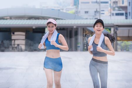 pursuing: Beautiful scenery of two female joggers pursuing their activity outdoors in the city in dusk