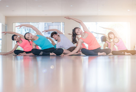Fitness Asian woman at stretching training at gym fitness center. Young slim girl makes aerobics exercise.Yoga Practice Exercise Class Concept Stock Photo