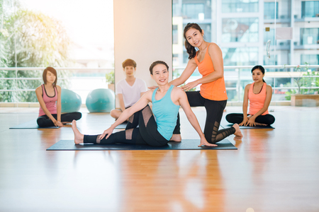 fitness, sport, training, gym and lifestyle concept - group of smiling women with trainer yoga stretching on mats in the gym.