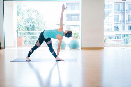 Portrait of beautiful young woman enjoying yoga indoors. Yogi girl working out in yoga studio twisting triangle Pose, Full length