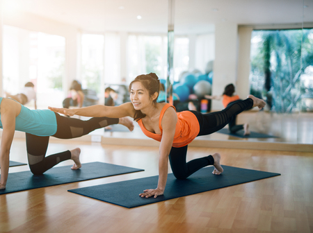 Aziatische vrouw het praktizeren yoga die binnen de gezondheid van de ontspanningsmeditatie uitrekt