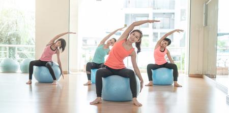 피트 니스 - 체육관에서 체조 공을 스포츠 훈련 또는 운동을 하 고 젊은 아시아 여성 파란색 안정성 공 여성 필 라 테 스 클래스 후면 거울보기