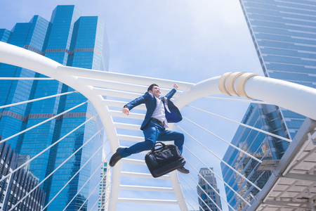 Successful businessman jumping with city town background.