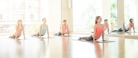 fitness, sport, training, yoga en mensen concept - Aziatische vrouw die zich uitstrekt op mat in gym.Group van vrouwelijke doen Yoga binnenshuis Stockfoto