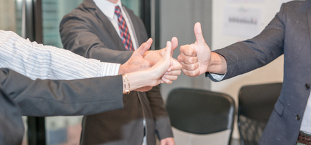 Business people give thumbs up sign