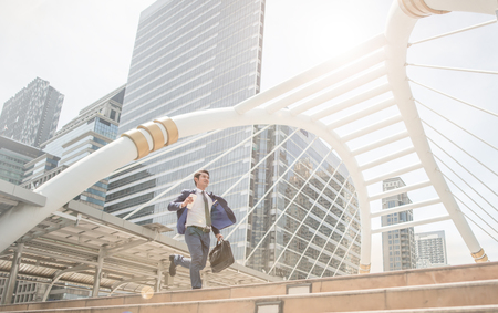 running business man in front of buildings hurry and rush because work late Stock Photo