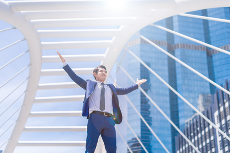 Celebrating success. Low angle view of excited young businessman keeping arms raised and expressing positive while standing outdoors with office building in the background