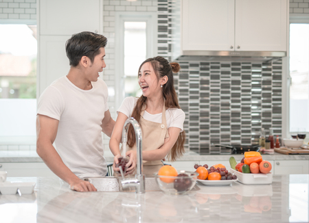 Happy young Asian woman washing fruit in the sink and handsome man standing next to her