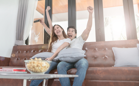 Asian couple watching TV sitting on a couch at home Stock Photo