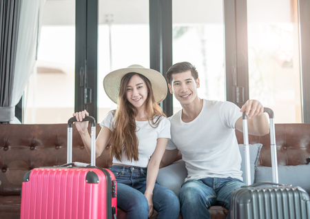 Elegant young Asian couple sitting waiting with baggage. vacation and traveler concept Stockfoto