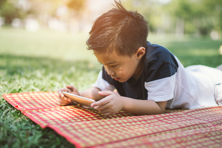 Kid palying smartphone in the park.