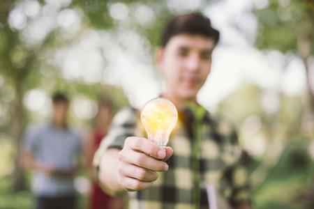 Man teen student holding to the illuminated bulb . Light Bulb Think Ideas Create .focus Light Bulb
