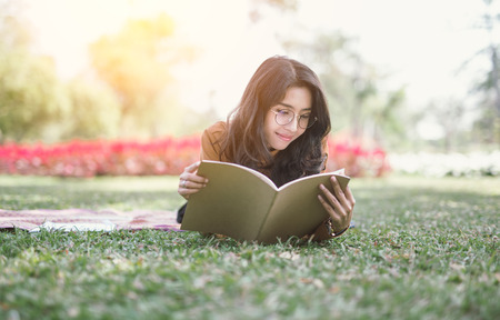 Portrait of high school girl lay down and read a book in park, education reading book concept