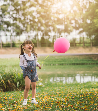 Portrait happy little girl with balloon walks in the park outdoors