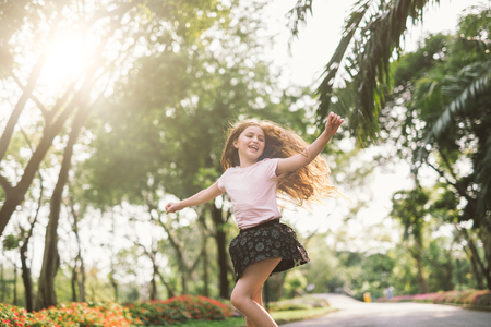 young girl with arms open enjoying her freedom at the park so happy relax dance Stock fotó - 97483144