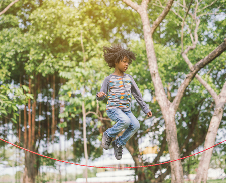 boy jumping over the rope in the park on sunny summer day Reklamní fotografie
