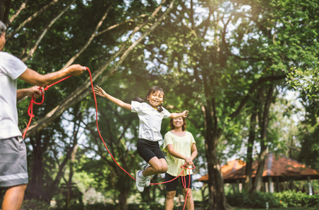 Summer vacation - happy family playing with skipping rope at green nature park