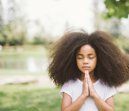 Afro child praying. Black kid prays. Gesture of faith.Hands folded in prayer concept for faith,spirituality and religion Stock Photo