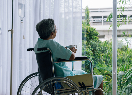 Senior man in a wheelchair alone in a room looking through the hospital window. Elderly patient