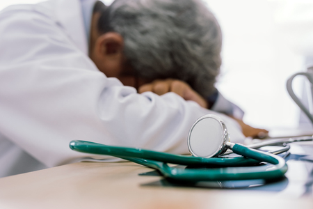 Senior doctor overwork Tired and sleeping on his deck at medical office
