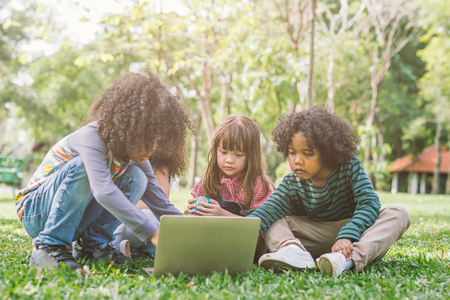 group of kids with laptop. happy children in nature with group of friend
