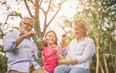 happy family in green nature park on summer ,grandfather blow soap bubbles along with grandchildren