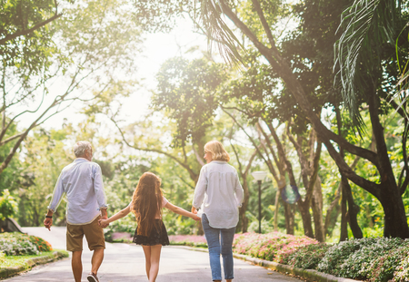 Family hold hand and walk on nature on sunset.