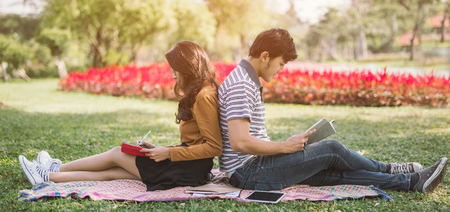 Asian couples reading a book .Campus life. Couple of students with a books. Education in nature park Stock Photo