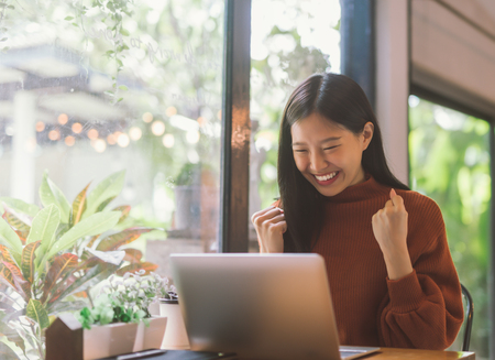 Young Asian woman celebrate success or happy pose with laptop Stock Photo