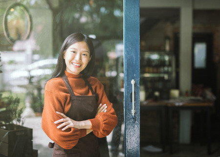 Beautiful asian woman store owner with standing in the doorway of her coffee shop looking at camera and smiling.Portrait of girl waitress wearing apron and standing in front