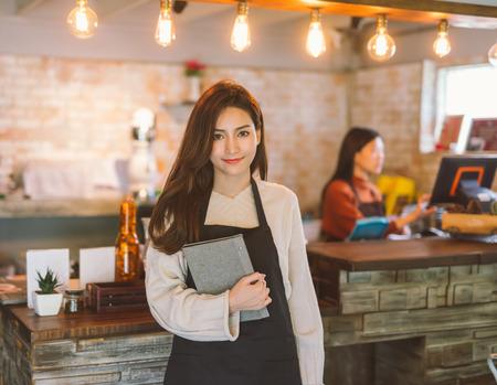 Retrato de camarera asiática sosteniendo menú con delantal y de pie en la cafetería.