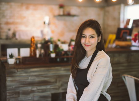 Portrait of Asian girl waitress wearing apron and standing in coffee shop. Stok Fotoğraf