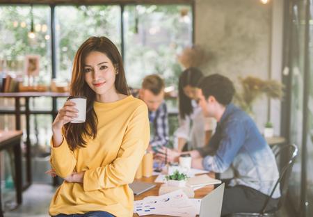 Retrato de la oficina de coworking del equipo de trabajo de la creatividad femenina asiática, sonriente de la taza de café de la explotación agrícola de la mano de la mujer hermosa feliz. Foto de archivo