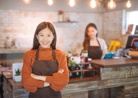 Retrato de camarera asiática sosteniendo menú con delantal y de pie en la cafetería. Foto de archivo