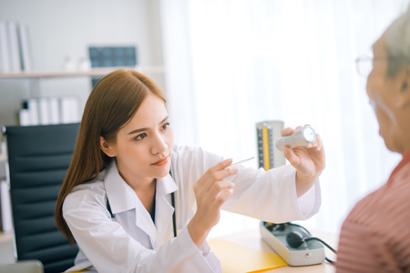 young female Asian doctor checking a patients throat