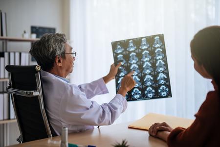 Médico asiático senior examinar imagen de resonancia magnética explicar al paciente
